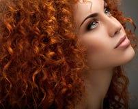 Красные волосы. Красивая женщина с курчавыми длинными волосами. стоковое изображение