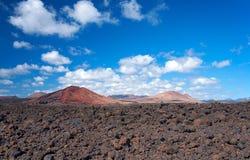Красные вулканы и горы на предпосылке темносинего неба с белыми облаками Поле черных вулканических бомб на переднем плане Стоковые Изображения RF