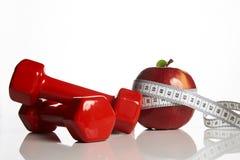 Красные гантели и красное яблоко с измеряя лентой Стоковое Изображение RF