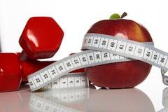 Красные гантели и красное яблоко с измеряя лентой Стоковые Фото