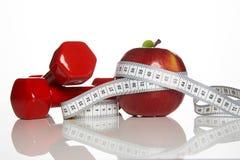 Красные гантели и красное яблоко с измеряя лентой Стоковая Фотография RF