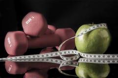 Красные гантели и яблоко окруженные лентой измерения на черноте Стоковое Фото