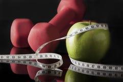 Красные гантели и яблоко окруженные лентой измерения на черноте Стоковые Изображения RF