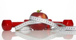 Красные гантели, свежая красная лента яблока и белых измеряя Стоковое Фото