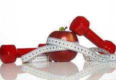 Красные гантели, свежая красная лента яблока и белых измеряя Стоковые Фотографии RF
