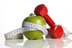 Красные гантели, свежее зеленое яблоко и измеряя лента Стоковое Изображение RF