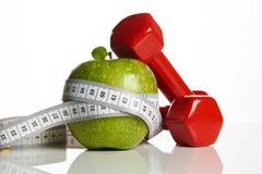 Красные гантели, свежее зеленое яблоко и измеряя лента Стоковое фото RF