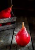 Красные груши на старой темной деревянной предпосылке Стоковые Изображения