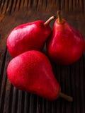 Красные груши на старой темной деревянной предпосылке Стоковое Изображение RF
