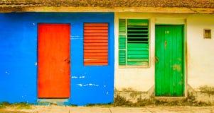 Красные дверь & окно на двери голубых соседей стены зеленой и окно o Стоковые Изображения