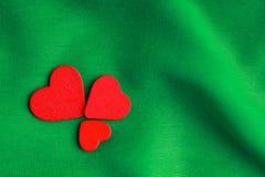Красные деревянные декоративные сердца на зеленой предпосылке створок. Стоковые Фотографии RF