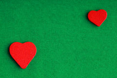 Красные деревянные декоративные сердца на зеленой предпосылке ткани Стоковая Фотография RF