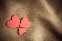 Красные деревянные декоративные сердца на коричневой предпосылке створок Стоковое Изображение RF