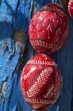 Красные деревянные пасхальные яйца над голубой корой дерева Стоковая Фотография