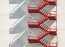 Красные лестницы пожарной лестницы на белом здании стоковые фото