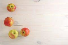 Красные желтые свежие яблоки на деревянной белой предпосылке Стоковые Изображения RF