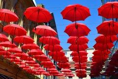 Красные зонтики приостанавливанные от установки на улицу Стоковые Изображения RF