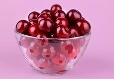 красные, зрелые, свежие вишни в стеклянном шаре на яркой розовой бумажной предпосылке Конец-вверх Стоковое Изображение