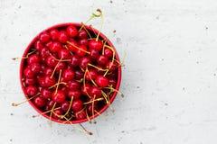 Красные зрелые вишни с кабелями в круговой плите на старой серой деревянной предпосылке с космосом для текста Стоковые Изображения