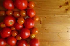Красные зрелые томаты и вишня на деревянном столе томаты courgettes предпосылки свежие vegetable Стоковое фото RF