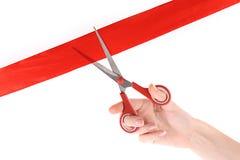 Красные изолированная тесемка, ножницы и рука Стоковые Фото