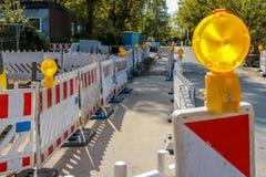 Красные и белые баррикады с предупредительными световыми сигналами на улице в re стоковые фотографии rf