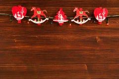 Красные и белые деревянные украшения рождества и света рождества на коричневой деревянной предпосылке Стоковые Изображения