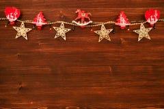 Красные и белые деревянные украшения рождества и света рождества на коричневой деревянной предпосылке Стоковые Фотографии RF