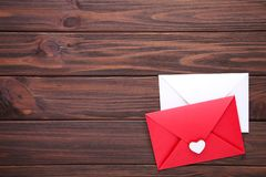 Красные и белые конверты на коричневой предпосылке стоковые фото