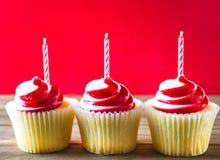 Красные и белые пирожные с свечами на деревянной предпосылке Стоковые Фото