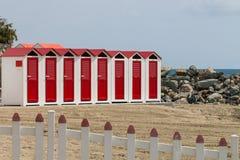 Красные и белые кабины и загородка пляжа Стоковое Фото