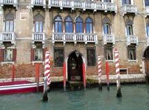 Красные и белые поляки зачаливания гондолы перед красивым зданием на грандиозном канале Венеции Стоковое Изображение RF