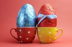 Красные и голубые пасхальные яйца в чашках многоточия польки Стоковая Фотография