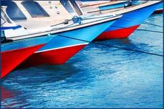 Красные и голубые старые рыбацкие лодки в морском порте Покрашенные отражения в воде солнце моря луча fiords предпосылки Стоковое Фото