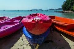 Красные и голубые шлюпки среди другого сплавляться на seacost в Таиланде Стоковые Изображения RF