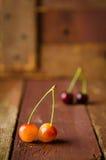 Красные и желтые вишни на деревянной предпосылке Стоковые Изображения
