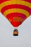 Красные и желтые горячие воздушные шары в полете напольно Стоковое Изображение