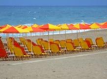 Красные и желтые Loungers и зонтики на песчаном пляже Стоковое Изображение RF