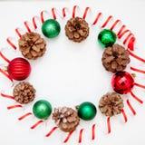 Красные и зеленые игрушки рождества, украшение, pinecone glitter белизна изолированная предпосылкой рамка круглая стоковые фото