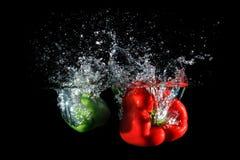 Красные и зеленые перцы падая в воду, изолированную на черноте Стоковые Фотографии RF