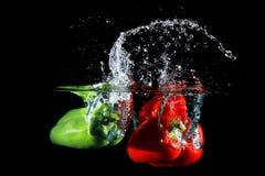 Красные и зеленые перцы падая в воду, на черной предпосылке Стоковые Изображения RF