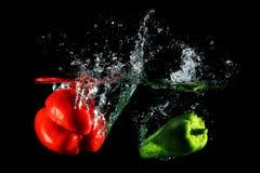 Красные и зеленые перцы падая в воду, на черной предпосылке Стоковая Фотография RF