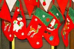 Красные и зеленые чулки рождества с снеговиком, santa и оленями стоковые изображения