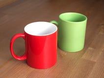 Красные и зеленые пустые кофейные чашки чая или на деревянном closup предпосылки Стоковое фото RF