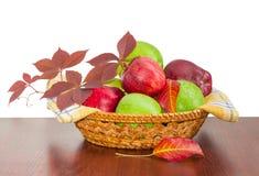 Красные и зеленые яблоки на checkered салфетке в плетеной корзине Стоковые Изображения