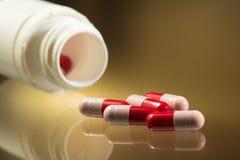 Красные и розовые капсула и бутылка probiotics Стоковое фото RF