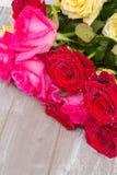 Красные и розовые розы на таблице Стоковые Изображения