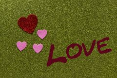 Красные и розовые sparkly сердца на зеленой предпосылке которая говорит влюбленность, Стоковые Фотографии RF