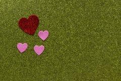 Красные и розовые sparkly сердца на зеленой предпосылке с космосом экземпляра Стоковая Фотография