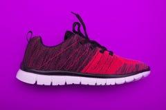 Красные и черные ботинки женщины спорта на фиолетовой предпосылке Стоковое фото RF